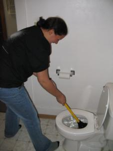 Denver plumbing customer demonstrates plunger usage